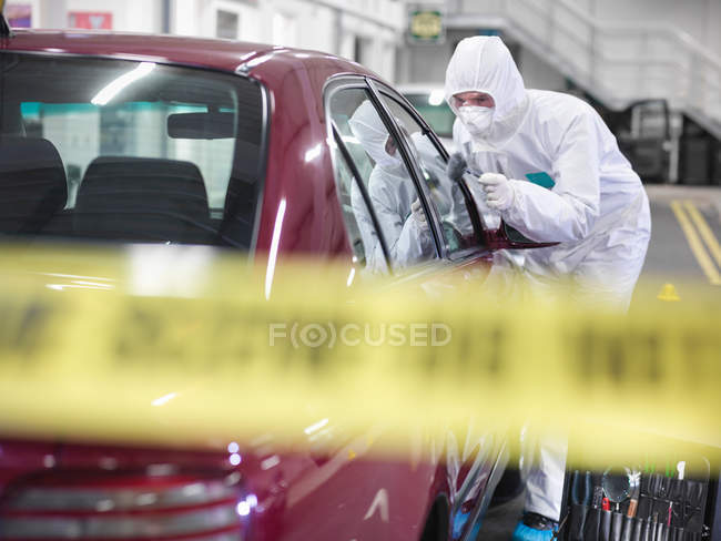 Forensic scientist dusting car for finger prints at crime scene — Stock Photo