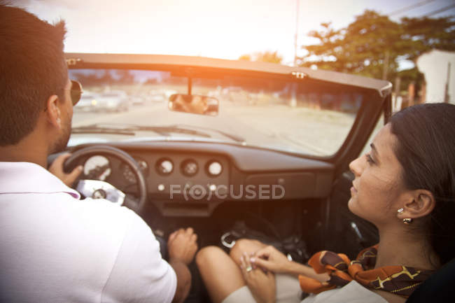 Mid adult couple in convertible car, rear view — Stock Photo