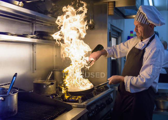 Chef with pan of flames in traditional Italian restaurant kitchen — Stock Photo