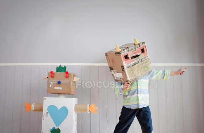 Karton-Roboter und junge in Roboter-Maske — Stockfoto