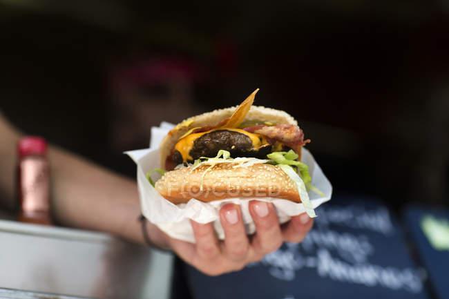 Man's hand serving hamburger from fast food van — стокове фото