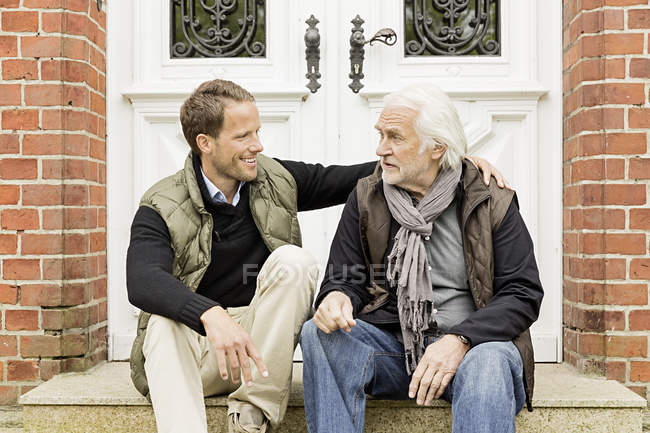 Father and son sitting on doorstep — Stock Photo