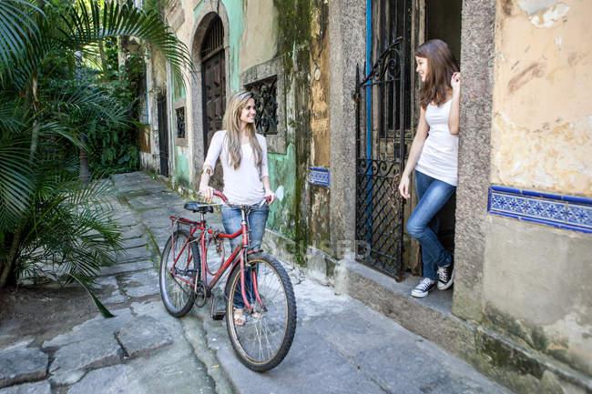 Молодая женщина с велосипедом разговаривает с другом в дверях — стоковое фото