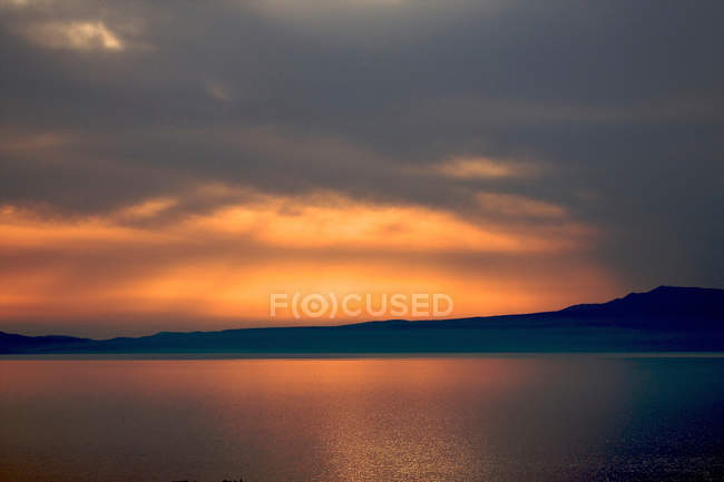 Golden sunset light in cloudy sky above sea and mountains — Stock Photo