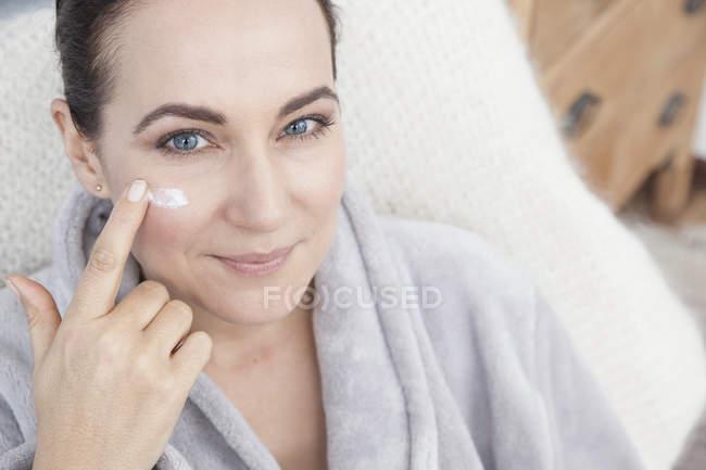 Donna matura che applica idratante al viso — Foto stock