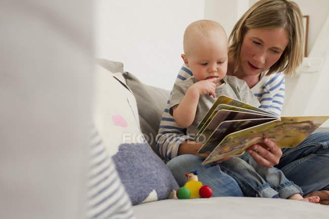 Madre madura y la hija bebé en el sofá de la sala de estar leyendo libro de cuentos - foto de stock