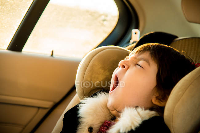 Young girl with eyes closed yawning in car — Stock Photo