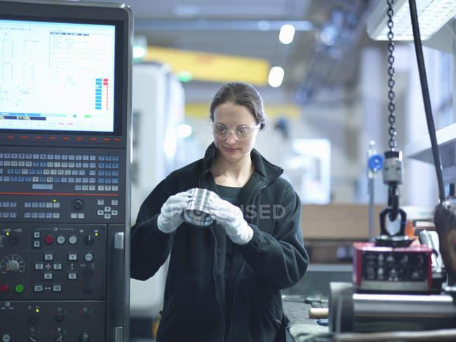 Mid adulto engenheiro feminino inspecionando parte na fábrica — Fotografia de Stock