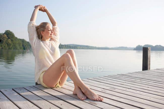 Mujer joven relajándose en el muelle del lago - foto de stock