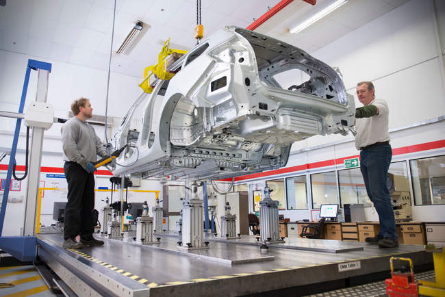 Workers placing car body on measuring machine in car factory — Stock Photo