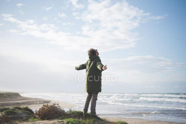 Hombre en dunas ventosas con los brazos abiertos, Sorso, Sassari, Cerdeña, Italia - foto de stock