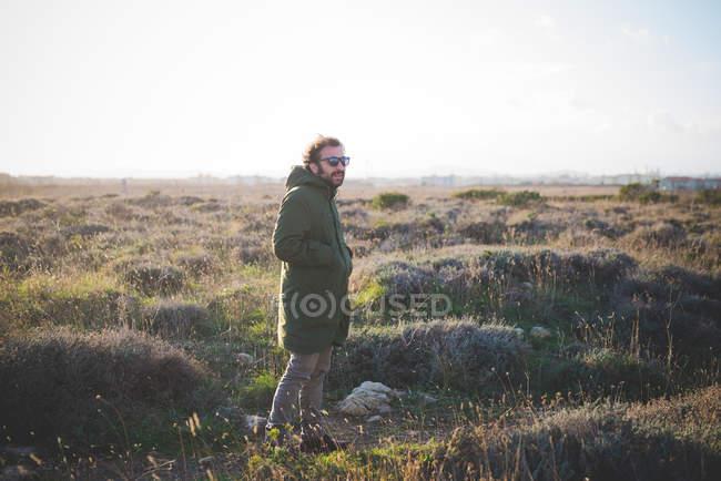 Одинокий мужчина средних лет с руками в карманах в поле — стоковое фото