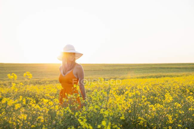 Серед дорослої жінки на полі каноли сонячний капелюх, що дивиться у бік — стокове фото