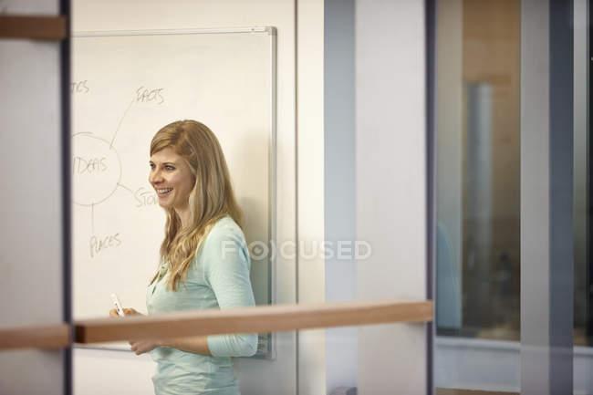 Femme d'affaires présentant des idées sur le tableau blanc dans le bureau — Photo de stock