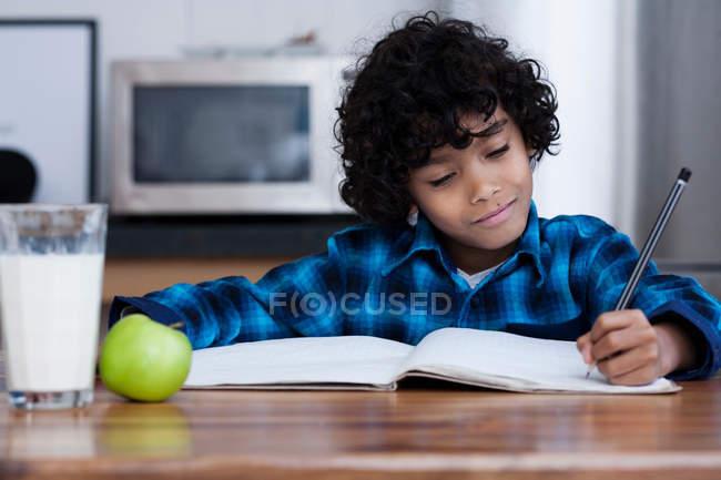 Garçon faire des devoirs à la maison — Photo de stock