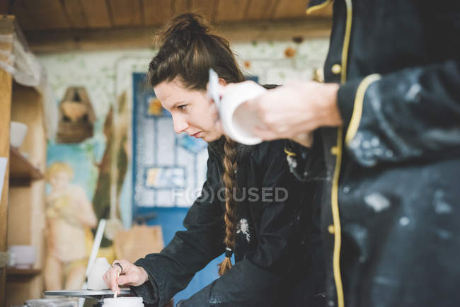 Side view of young woman in workshop stirring ceramic glaze, looking away — Stock Photo