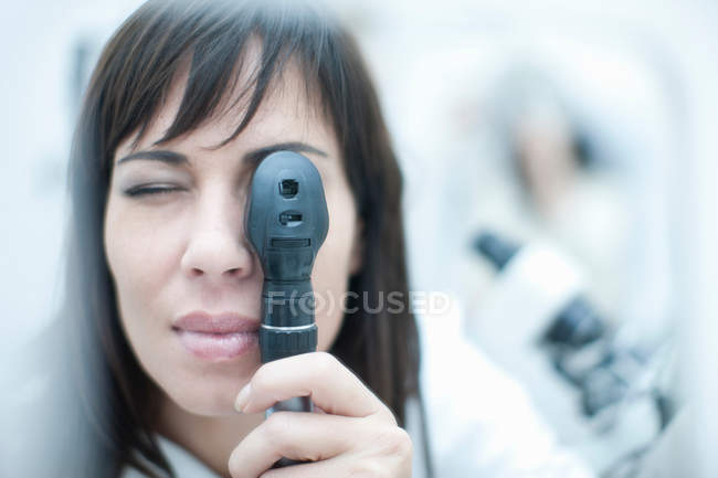 Optician looking through ophthalmoscope — Stock Photo