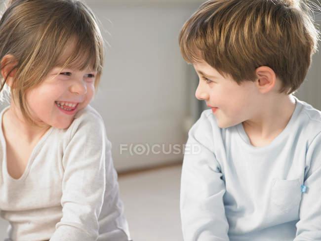 Crianças que sorriem junto dentro — Fotografia de Stock