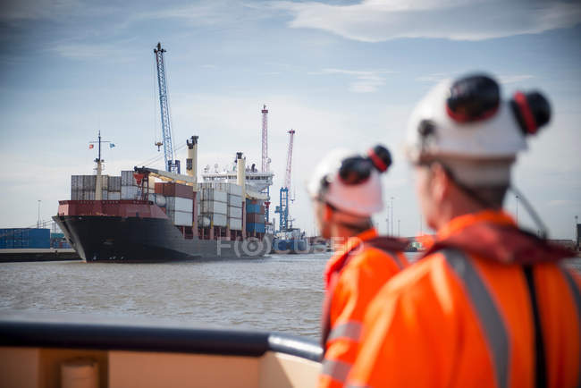 Tug workers on tug with container ship in background — Stock Photo