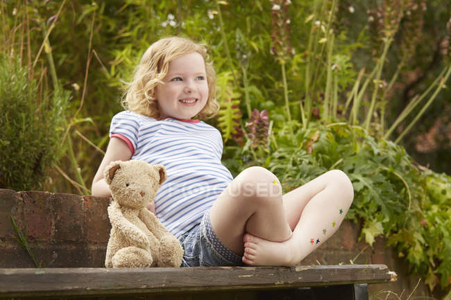Girl on garden seat with teddy bear and star stickers on legs — Stock Photo