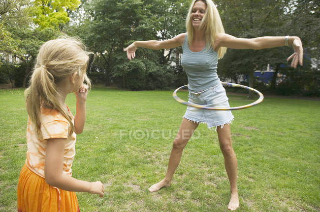 Дівчина дивиться мати Хула hooping на зелений газон — стокове фото