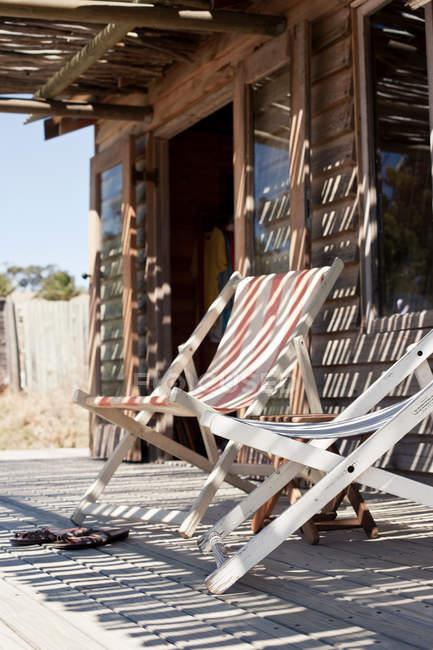 Cadeiras de praia no convés fora da cabana de praia — Fotografia de Stock