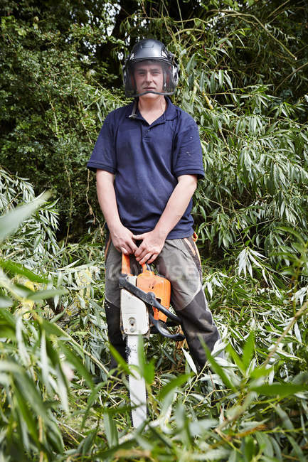 Worker holding chainsaw in forest — Stock Photo