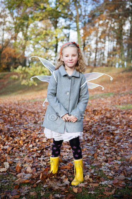 Portrait of girl wearing fairy wings in park — Stock Photo