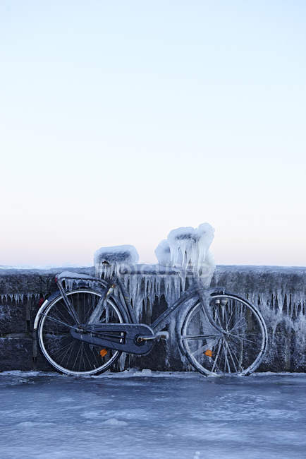 Bicycle leaning against wall and covered in ice — Stock Photo