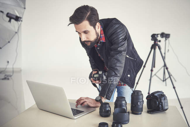 Male photographer reviewing studio photo shoot on laptop — Stock Photo