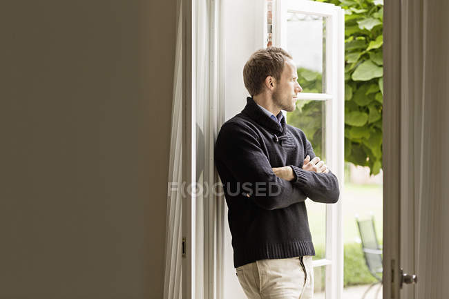 Mid adult man looking out of window, arms folded — Stock Photo