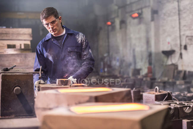 Worker inspecting hot molten metal in moulds in foundry — Stock Photo