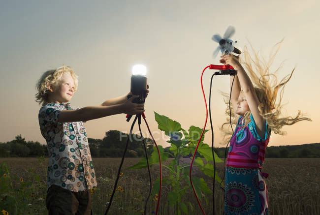 Brother and sister generating light from wind power — Stock Photo