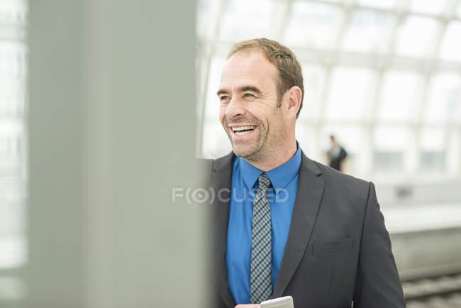 Бізнесмен в костюмі, сміючись дивлячись геть — стокове фото