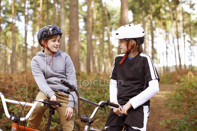 Twin brothers on BMX bikes chatting in forest — Stock Photo