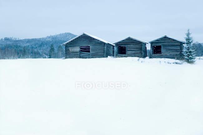 Case di legno in campo innevato — Foto stock