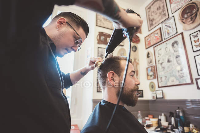 Barber drying client hair in barber shop — Stock Photo