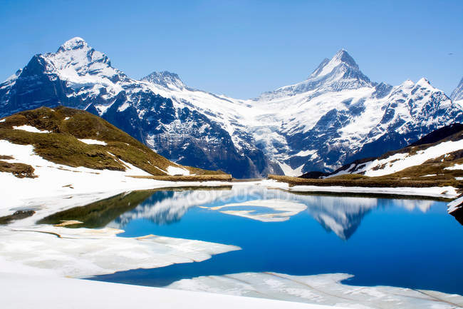 Snowy landscape reflected in lake — Stock Photo