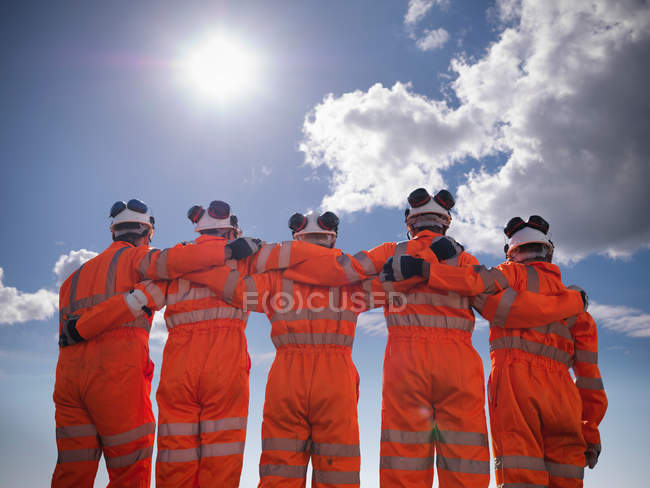 Залізничні працівники носять високу видимість одягу з обіймами навколо один одного, низький кут — стокове фото