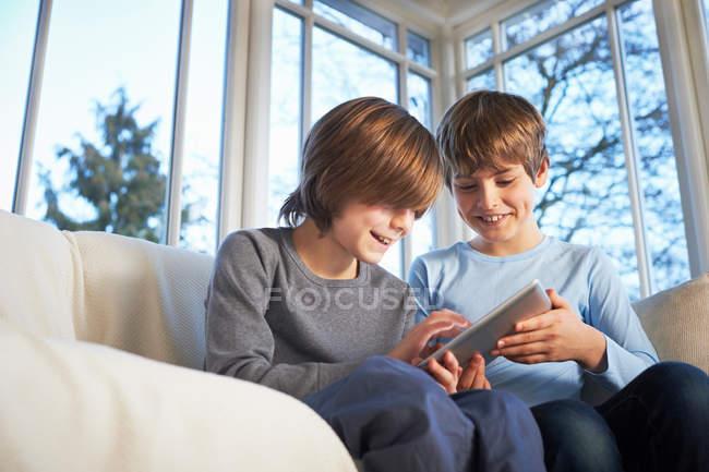 Fratelli che utilizzano tablet digitale insieme — Foto stock