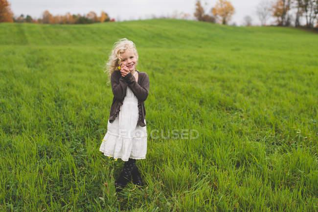 Портрет маленькой девочки в зеленом поле с цветами осенью — стоковое фото