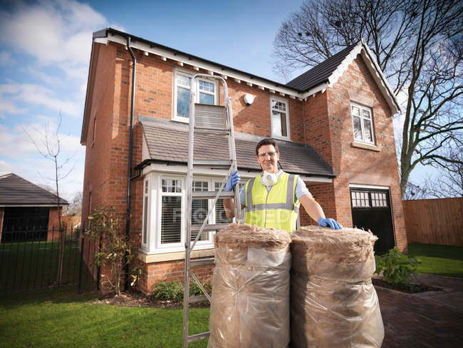 Man with loft insulation and ladder in front of house — Stock Photo
