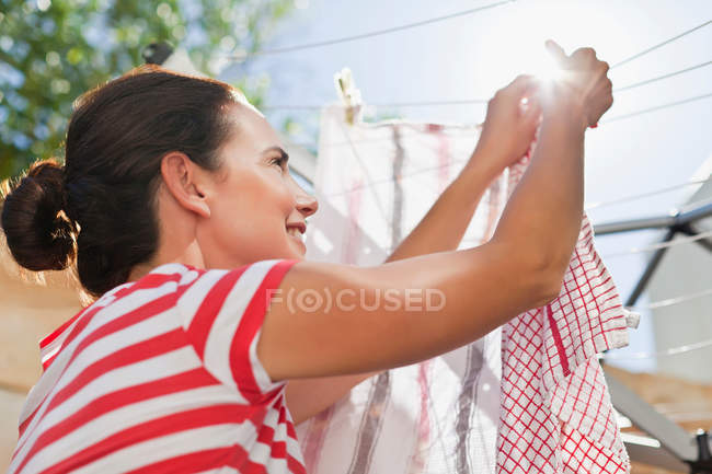 Woman hanging clothes up on line — Stock Photo