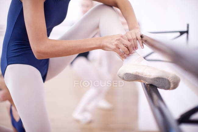 Ballerina fastening ballet slipper — Stock Photo