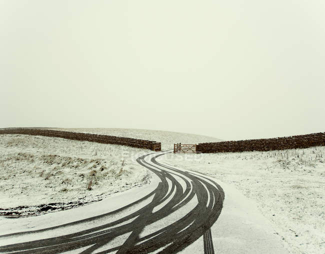 Tire tracks on snowy rural road with fencing and gate — Stock Photo