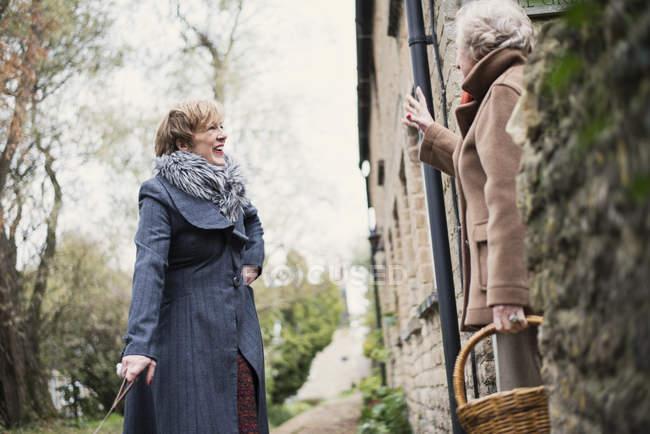 Літня жінка вітання старша жінка на вулиці міста — стокове фото