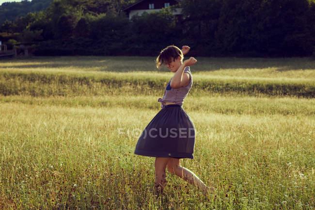 Jeune femme marchant dans la prairie — Photo de stock