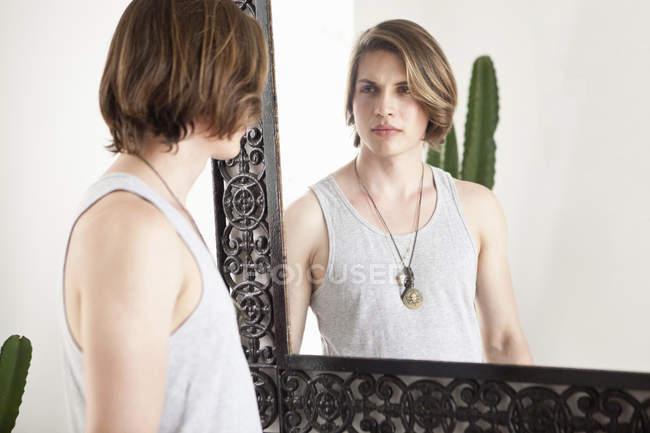 Joven mirando la imagen del espejo en el vestíbulo del hotel - foto de stock
