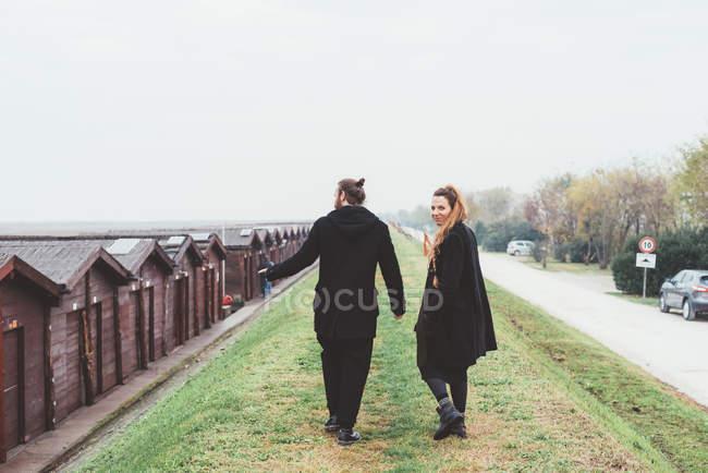 Vista trasera de pareja paseando por terraplén - foto de stock