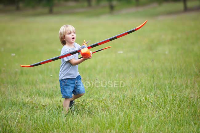 Niño jugando con el avión de juguete al aire libre - foto de stock